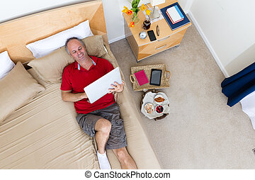 Man Lying on Bed with Laptop in Hotel Room
