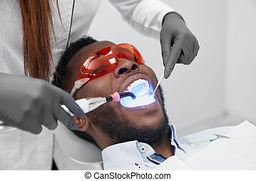 Man lying on dentist chair in protective glasses in clinic