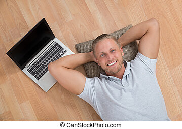 Man Lying On Floor With Laptop