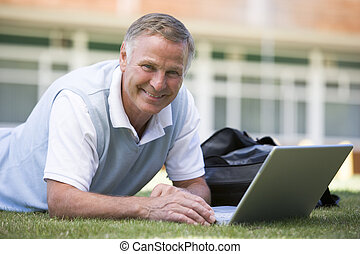 Man lying on lawn of school with laptop