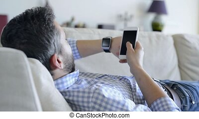 Man lying on sofa using smartphone and smart watch