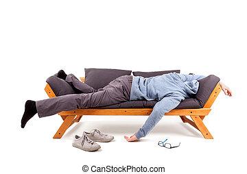 Man lying on sofa with hangover.