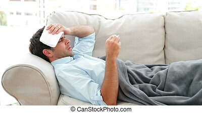 Man lying on the couch sick