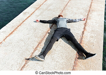 Man lying on the dock. above view