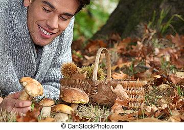 Man lying on the floor picking mushrooms