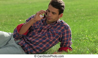 Man lying on the grass using mobile