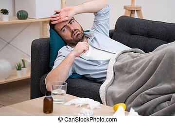 Man lying on the sofa feeling sick illness at home