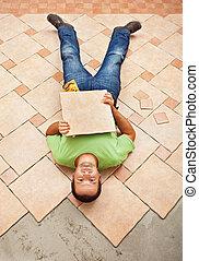 Man lying on unfinished floor tiling