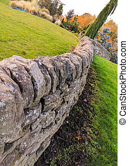 A brick wall that has been carefully constructed in well kept gardens where visitors come from all around to enjoy the views.