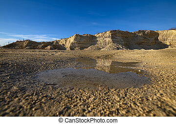 Man made limestone cliffs reflected in puddle at limestone quarry
