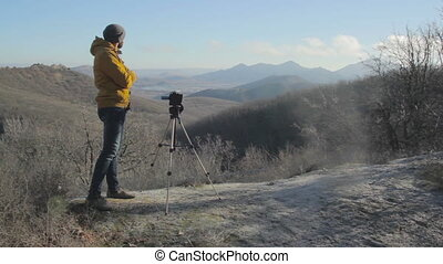 Man make a shot of landscape with camera on the tripod at...