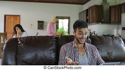 Man Make Online Video Call Using Tablet Computer Sit On Coach In Living Room, Latin Guy Speaking Internet Communication