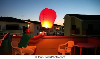 Man make some sort of flying baloon, he put some fire at...