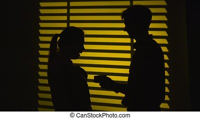 Man makes a gift to a woman and gets a kiss. Silhouette. Slow motion. Close up