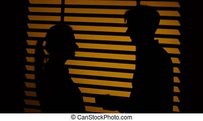 Man makes a gift to a woman. Kiss couple. Silhouette. Close up