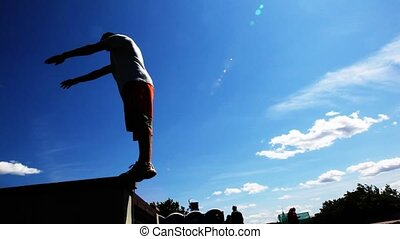 Man makes back flip, sportsman trains on outdoor - young man...