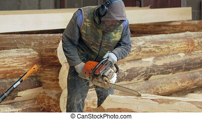 Man makes curly cutting wood Chainsaw. The log will be part of the future of the wooden house.