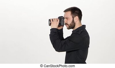 Photographer releases the shutter in the studio, a young man stands in profile and he holds a camera, human trying to get a good picture, on white background