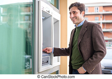 Man making a cash withdrawal from atm bancomat service