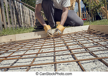 Man making a net of steel bars by clipping them together...