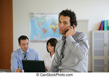 Man making a phone call with colleagues in the background