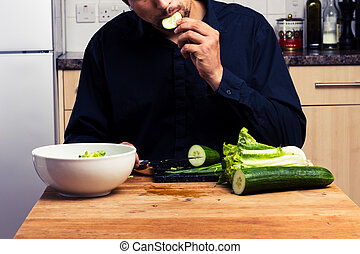 Man making a salad and eating cucumber
