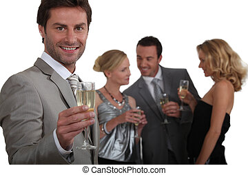 Man making a toast with champagne as his friends chat in the background