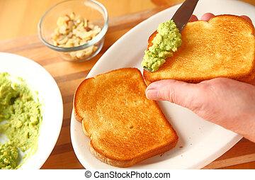 Man making avocado toast closeup