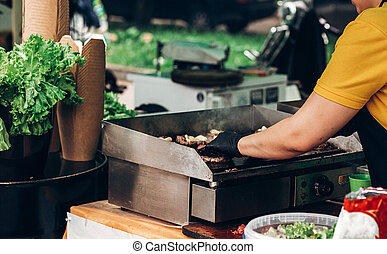 man making burgers, roasting meat and vegetables on grill. chef in form cooking  juicy beef pork for sandwiches. street food festival. summer picnic. grilling barbecue