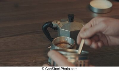 Man making coffee in the coffee machine geyser, a hand shoots prepared coffee from the stove