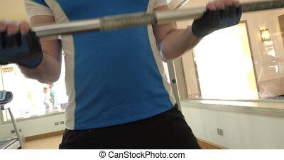 Man making efforts in exercise with crossbar - Tilt shot of...
