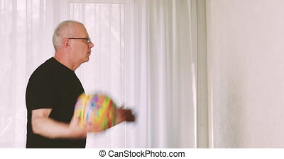Man making exercises with a ball staying at home