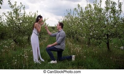 Man making marriage proposal to woman in orchard - Handsome...