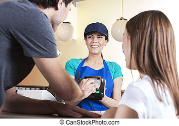 Man Making NFC Payment While Standing With Daughter And Waitress