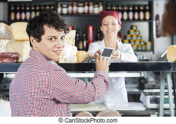 Man Making Payment To Saleswoman In Cheese Shop