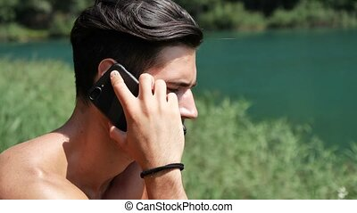 Man making phone call at lake
