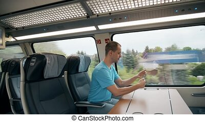 Man making photo with his smartphone while travelling by train