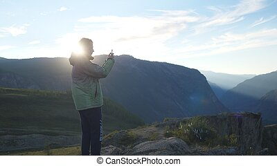 Man making photos with smart phone on peak of rock in the mountains with lens flare effects.