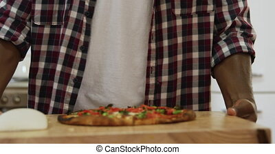 Man making pizza at home - Front view mid section of a...
