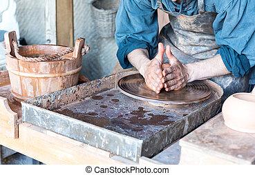 Man making pot on potter wheel in a workshop
