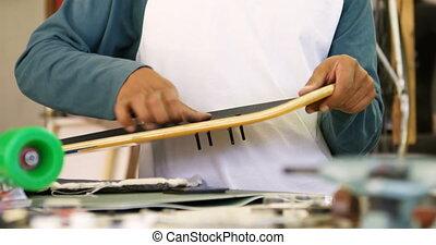 Man making skateboard 4k - Man making skateboard in workshop...
