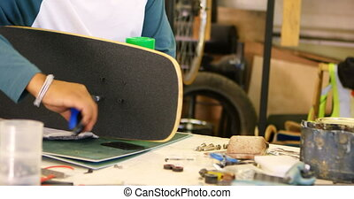 Man making skateboard 4k - Man making skateboard in workshop...