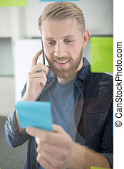 man making telephone call and reading post-it note reminder