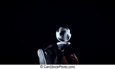 Man making tricks with ball in twilight. Slow motion