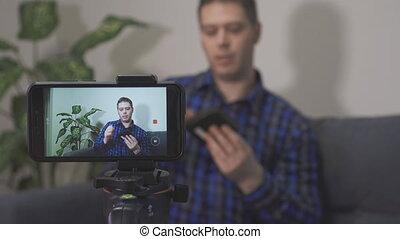 Man making video blog about external hard drive.