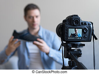 Man making video blog about shoes. Focus on camera.