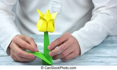Man making yellow origami flower. Close up. Yellow tulip.