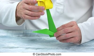 Man making yellow origami tulip. Origami flower with green...