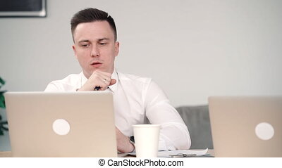 man manager with vaping an electronic cigarette in office working with laptop and talk to colleague