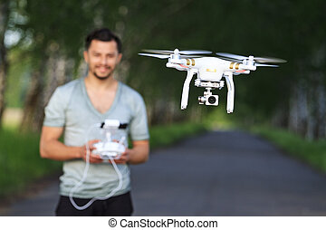 man manages drone in bright sunny day
